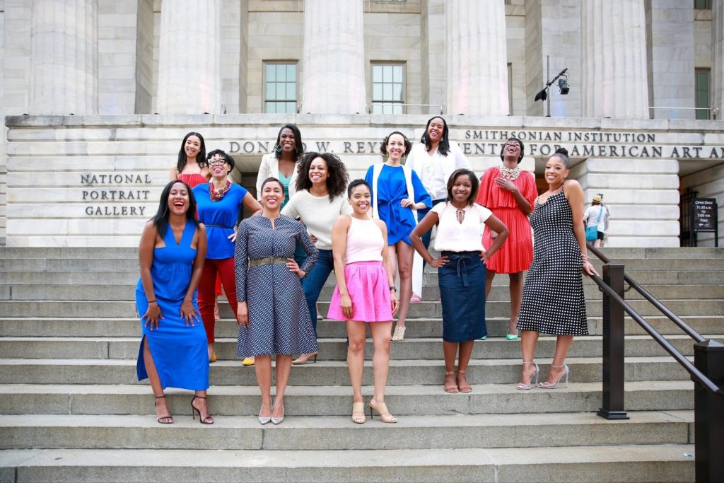 Ashleigh stands in the center of 12 women on the steps of the National Portrait Gallery, posing as one of the Black Girl 44 Scholarship donors.