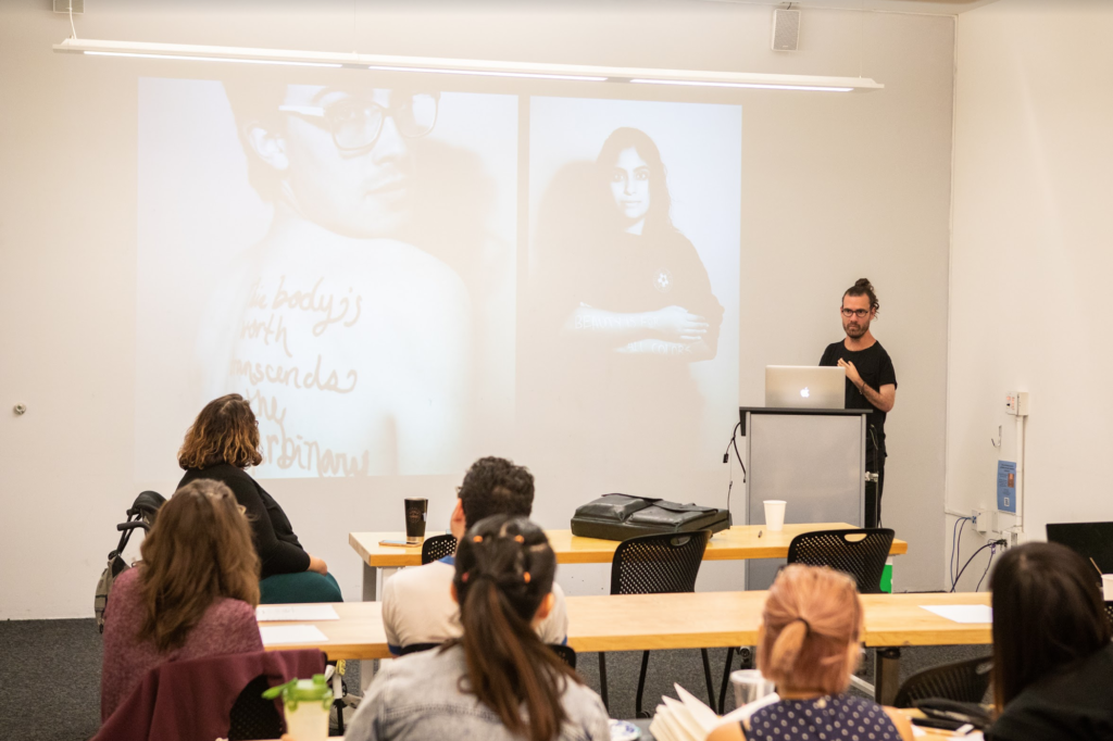 "Josh giving a lecture to design students at California College of the Arts. He is joined by co-organizer, Catherine Callahan. The slide features Hannah Soyer's This Body is Worthy project—an ongoing campaign celebrating bodies that fit outside social ideals. The subject at left showcases a written message on their back: ""This body's worth transcends the gender binary."" The subject at left has ""Beauty is for all colors."" scribed on their folded arms."