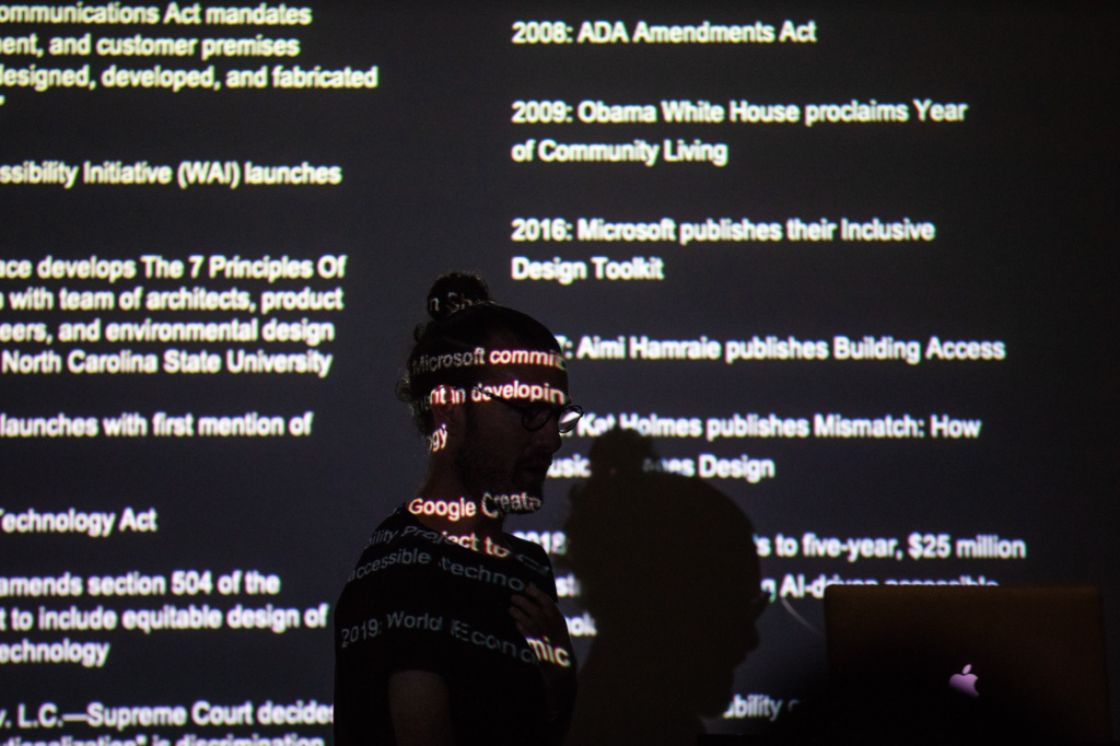 Josh walking in front of a slide which is projected on top of his face. Almost completely black, his figure is silhouetted and a timeline of significant disability design events are featured on the screen including the passage of the ADA and Microsoft's recent $25-million investment in accessible technology.